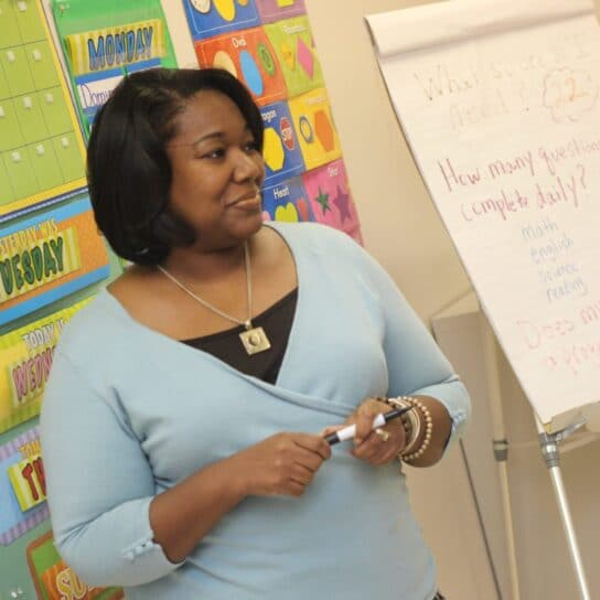 Teacher delivering exciting lesson to primary students